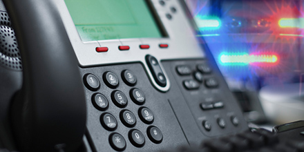 Business landline phone with police lights in the background