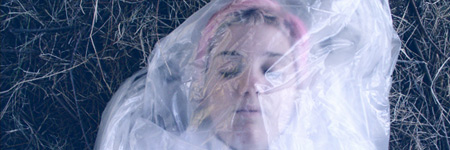 Pink-haired young woman wrapped in clear plastic and lying on the grass