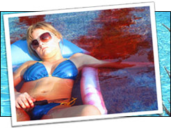 Girl in bikini lying on a raft in a pool with blood evident in the water