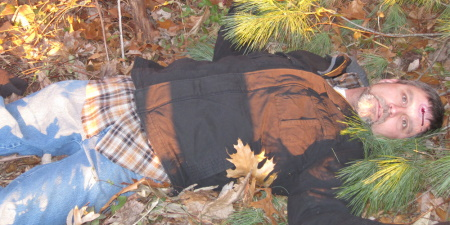 Man with a gunshot wound lying dead in the woods